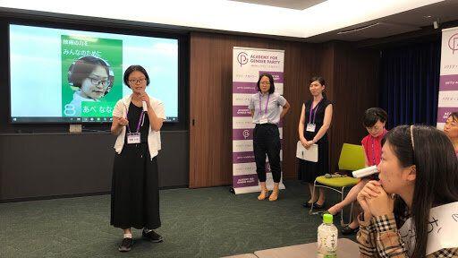 韓国のフェミニスト政治家のポスターをイメージしたキャンペーンを展開する対立候補(左)を見つめるチームの候補者(右)