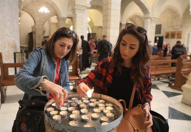 Dos mujeres palestinas cristianas encienden velas en la Iglesia de Santa Catalina, anexa a la Natividad,...