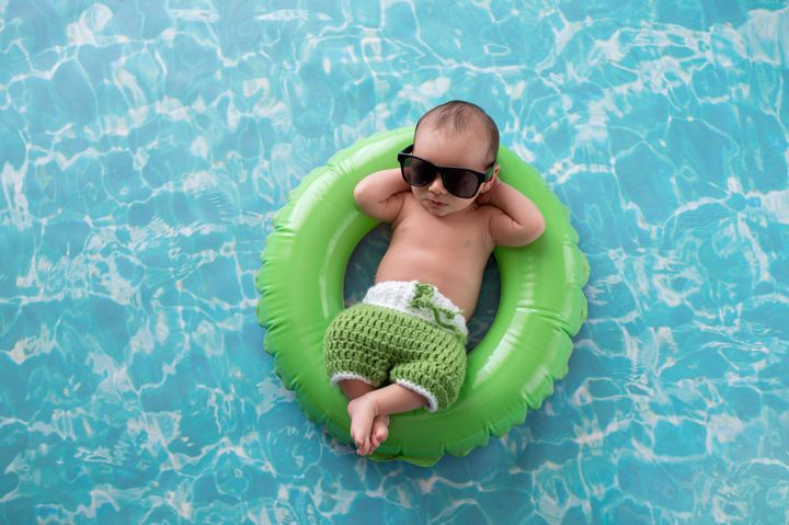 Two week old newborn baby boy sleeping on a tiny, green, inflatable swim ring. He is wearing green, crocheted board shorts and black sunglasses.