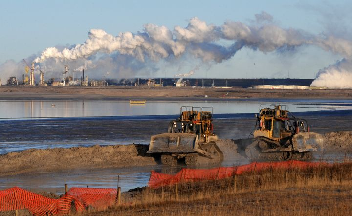 Workers use heavy machinery at a composite tailings pit at the Syncrude oilsands extraction facility near Fort McMurray, Alta. on Oct. 25, 2009. Imperial Oil owns 25 per cent of the development.
