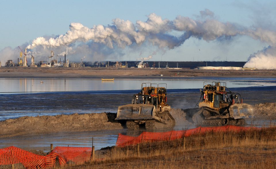 Workers use heavy machinery at a composite tailings pit at the Syncrude oilsands extraction facility...