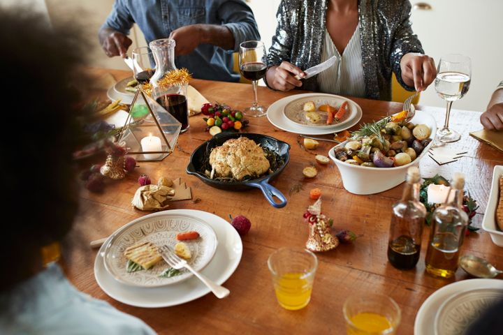 Midsection of couple having lunch on dining table at home during Christmas festival
