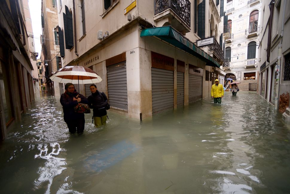 People walk across flooded streets on Nov. 15, 2019 in Venice, two days after the city suffered its highest tide in 50 years.