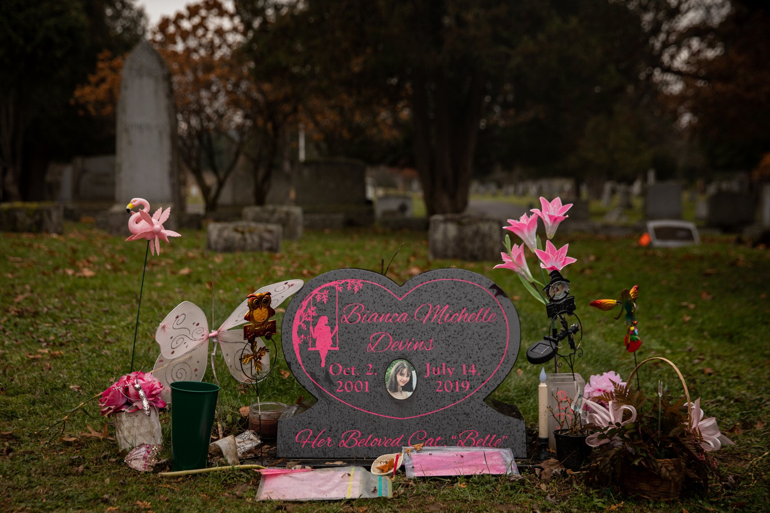 The headstone for Bianca Devins is covered in flowers and tokens from friends and family.