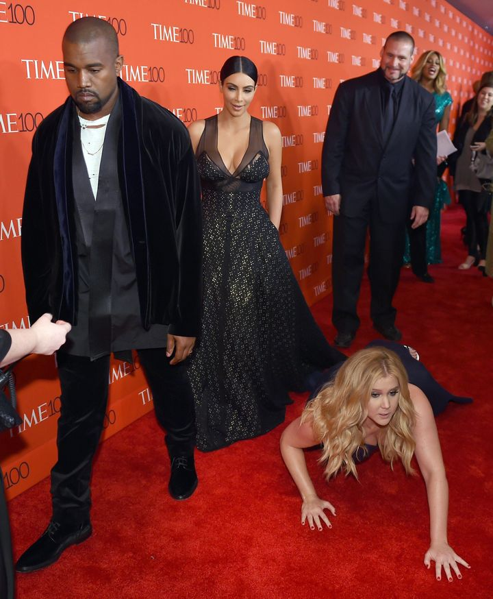 Schumer pretends to trip and fall on the floor in front of honorees Kim Kardashian and Kanye West as they attend the Time 100