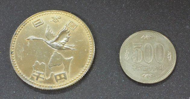 謎のメダル(左)と500円硬貨の比較。「日本国」「千円」の刻印が確認できる。