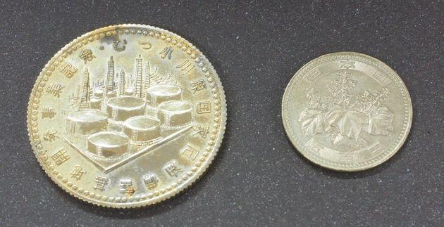 謎のメダル(左)と500円硬貨の比較。こちらの面には「むつ小川原国家石油備蓄基地開発記念」と刻印されている。