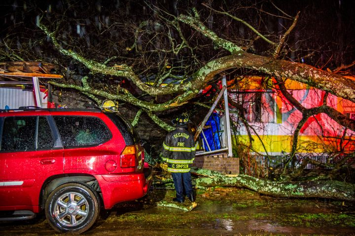 Cory Simpson of Decatur Fire & Rescue assess damage before evacuating a mobile home after a tree fell on the home in Deca