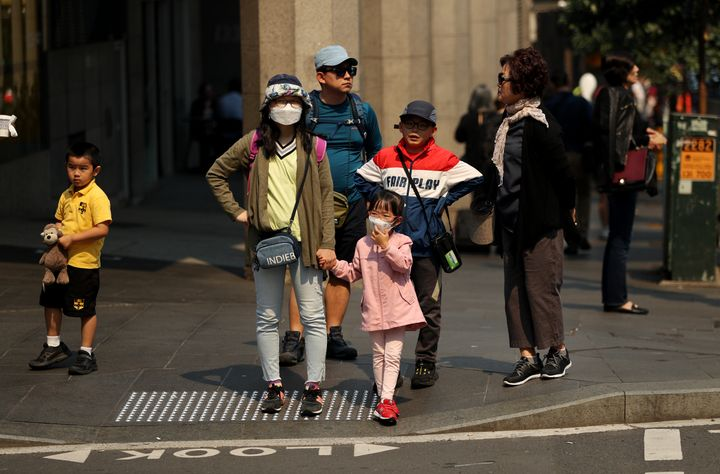 A family wear face masks as protection from the smoke haze in Sydney, Australia.