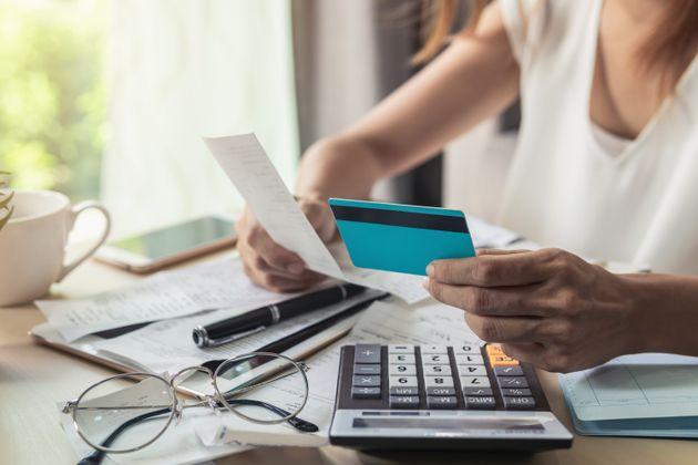 Young woman checking bills, taxes, bank account balance and calculating credit card expenses at