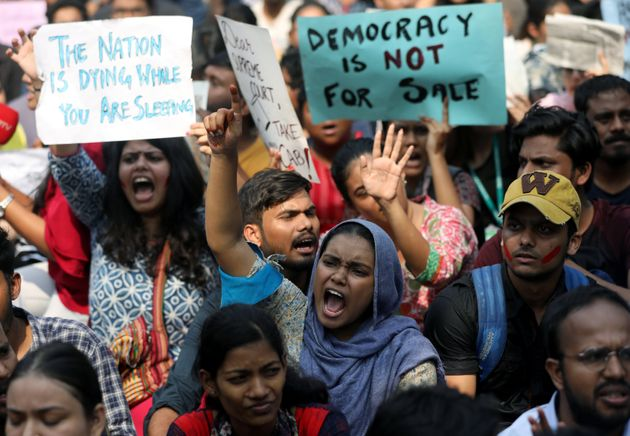 Students hold placards and shout slogans in solidarity with Jamia Millia Islamia university students,...
