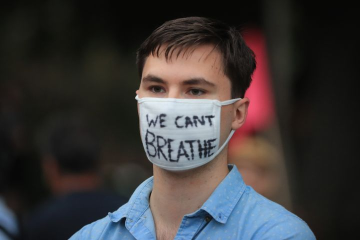 A protester wearing a mask at a rally for climate action at Sydney Town Hall on 11 December.