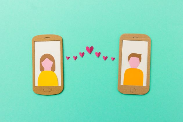 Online dating and mobile flirting concept - man and woman profile on smartphones connected with flying...