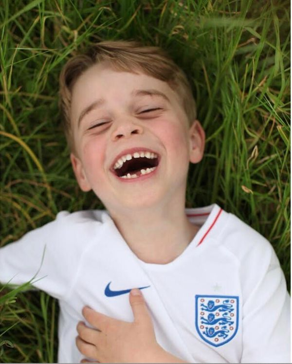 Prince George laughs in the garden of his home at Kensington Palace in this photo released ahead of his sixth birthday in Jul