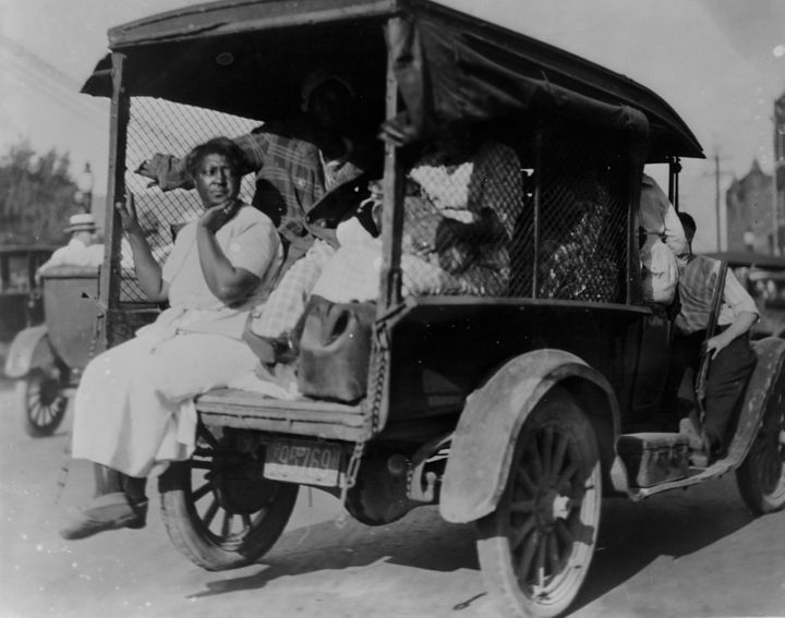 A woman seated on the back of a small truck loaded with people during the 1921 Tulsa race massacre.