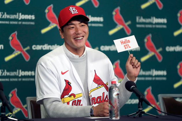 St. Louis Cardinals pitcher Kwang-Hyun Kim smiles as he holds up a sign during a news conference Tuesday,...