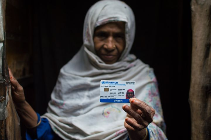 A Rohingya woman, who fled from ongoing military operations in Myanmars Rakhine state, holds up her refugee card issued by the UNHCR at a refugee camp in Madanpur Khadar district of Delhi, India on September 22, 2017.