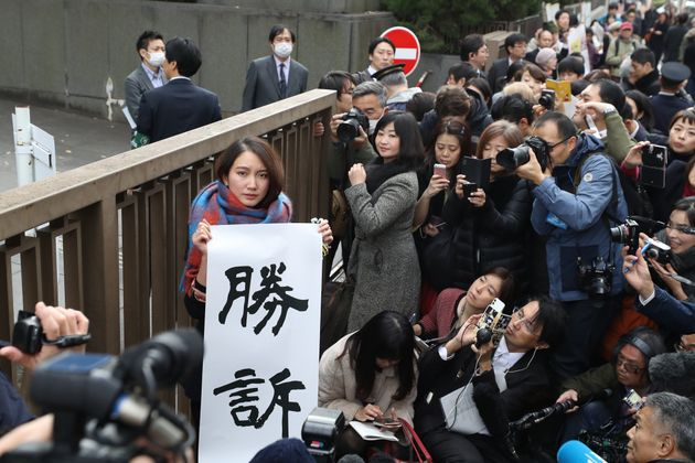 TOKYO, JAPAN - DECEMBER 18: Shiori Ito holds up signs showing victory in front of the Tokyo District...