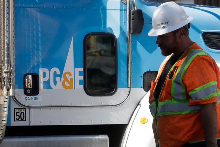 A Pacific Gas & Electric worker walks in front of a truck in San Francisco, Thursday, Aug. 15, 2019.