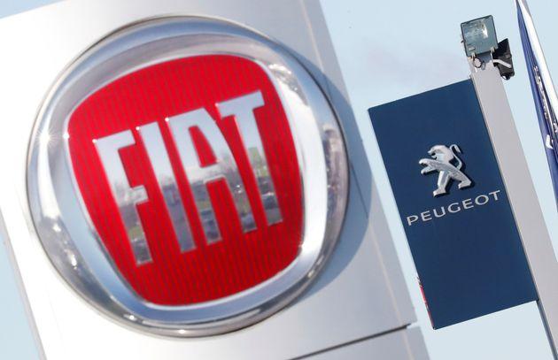 Les logos des constructeurs automobiles Fiat et Peugeot devant les concessionnaires des entreprises à...