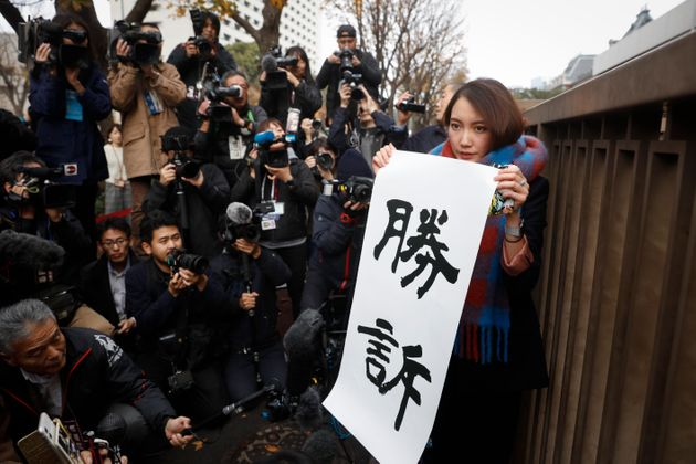 Freelance journalist Shiori Ito holds a banner that reads in English