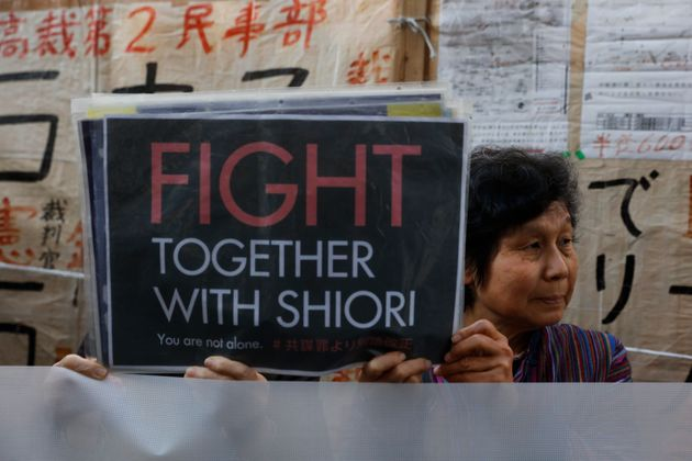 Two supporters of freelance journalist Shiori Ito hold signs outside a courthouse Wednesday, Dec. 18,...