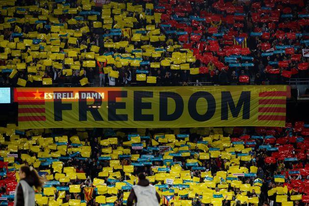 Una de las grandes pancartas y multitud de pequeñas con la leyenda 'Spain, sit and talk' en el...
