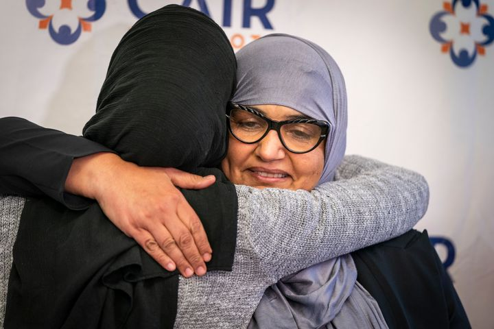 Aida Shyef Al-Kadi, right, hugs Asma Mohammed, advocacy director at Reviving the Islamic Sisterhood for Empowerment, after a