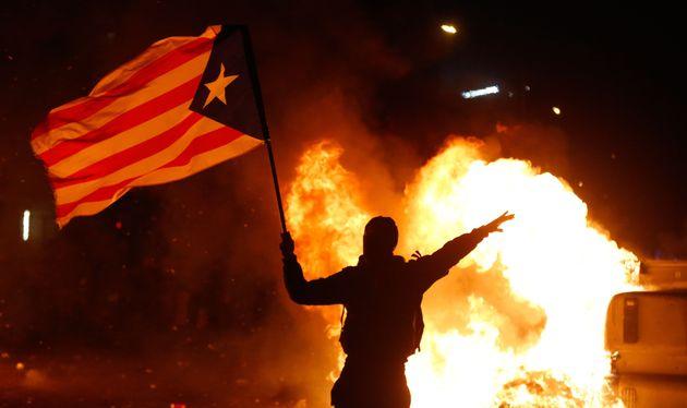 Un manifestant brandit un drapeau catalan près de bennes à ordures en feu à côté...