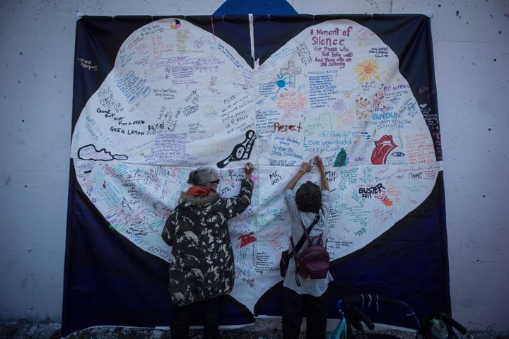 Women write messages on a banner during a memorial service to remember those who have died in the province as a result of the drug overdose crisis, on International Overdose Awareness Day in Vancouver's Downtown Eastside on Aug. 31, 2017.