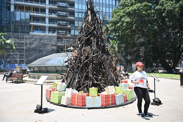 A volunteer collects donations in front of an an installation dubbed 'the Burnt Christmas Tree' to support...