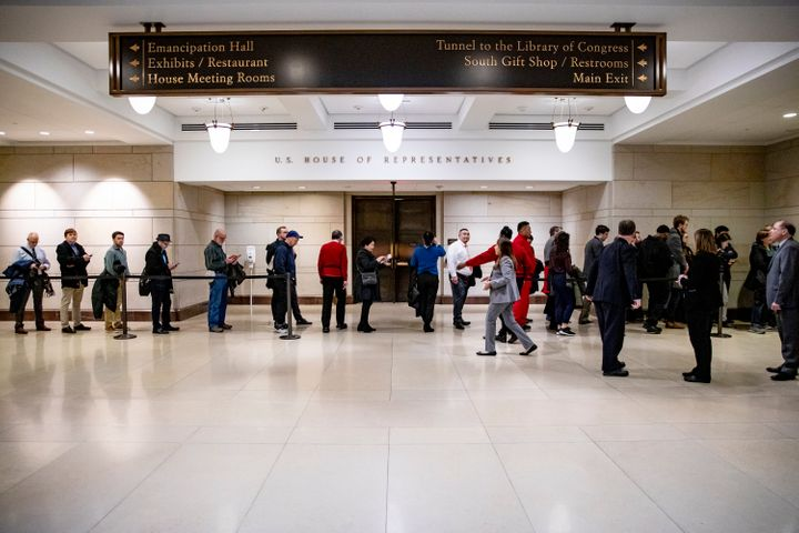 Tourists wait in line for a chance to get into the House chamber to watch lawmakers vote to impeach President Donald Trump.