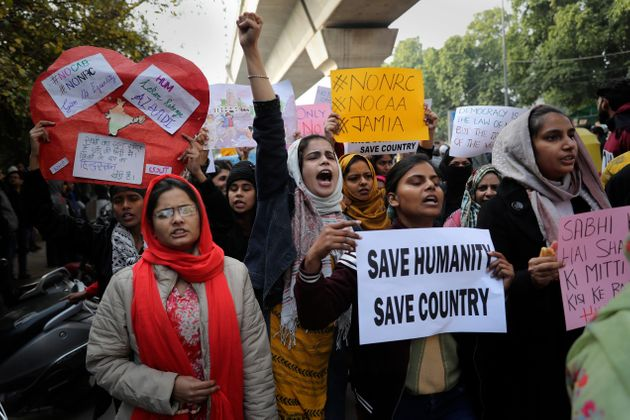 Indian students of the Jamia Millia Islamia University shout slogans as they march during a protest,...