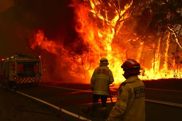 Fire crews on scene as a bushfire burns next to a major road and homes on the outskirts of the town of Bilpin in Sydney on Friday