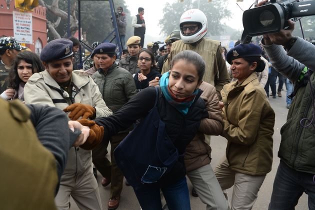 Police detain a woman at a demonstration against CAA in New Delhi on December 19,