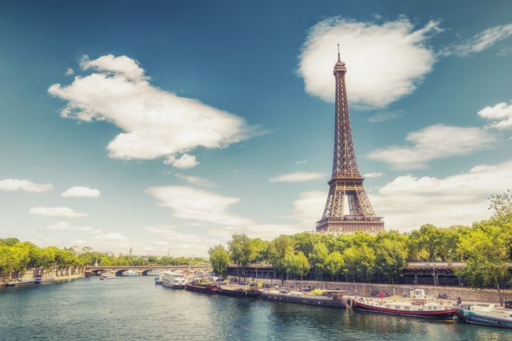 The Eiffel Tower in Paris, France, on a summer day with the river Seine and dramatic clouds. Colourful travel background.