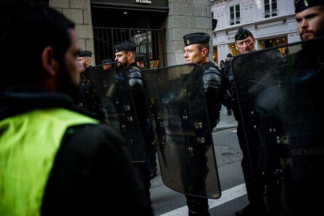 Un gilet jaune face à des policiers lors d'une manifestation à Rennes le 14 décembre