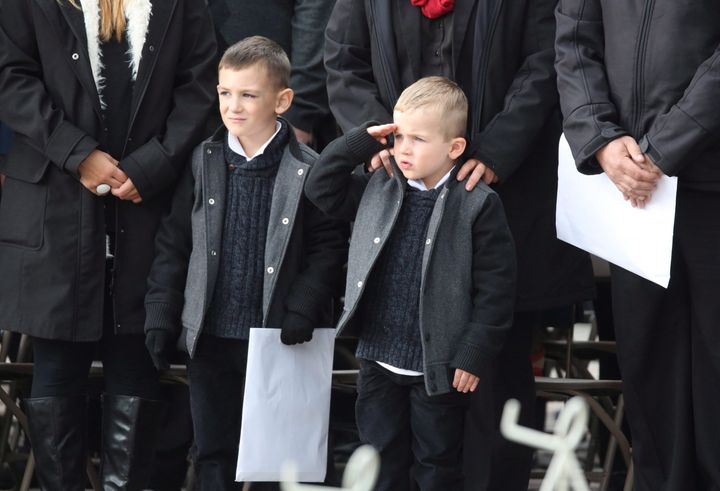 Marcus Cirillo (left), son of Cpl. Nathan Cirillo, stands next to Cameron Cirillo as he salutes during a ceremony marking the one year anniversary of the attack on Parliament hill on Oct. 22, 2015 at the National War Memorial in Ottawa.