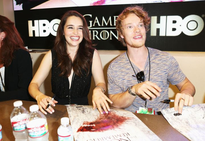 "Emilia Clarke and co-star Alfie Allen sign autographs for ""Game of Thrones"" during Comic-Con International in 2012."