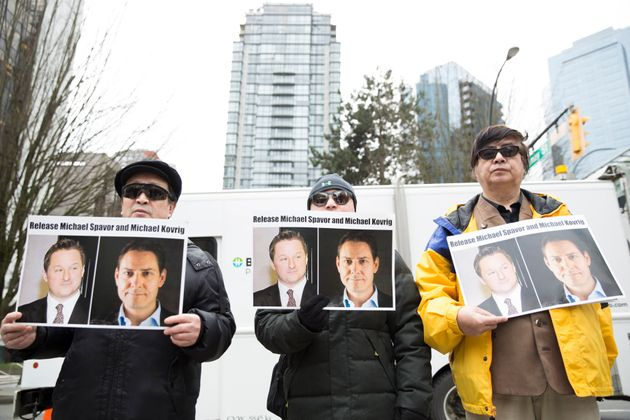 Protesters hold photos of Michael Spavor and Michael Kovrig in Vancouver on March 6,
