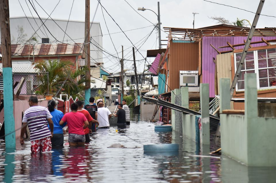 People walk in a flooded street next to damaged houses in Puerto Rico on Sept. 21, 2017, after Hurricane...