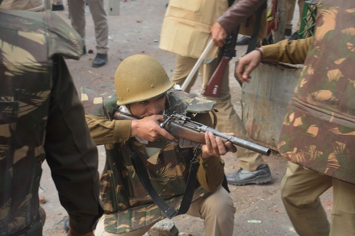 A police personnel aims his gun towards protesters during demonstrations against India's new citizenship law in Meerut on December 20, 2019. - Five more protesters died in fresh clashes on December 20 between Indian police and demonstrators, taking the death toll to 14 from more than a week of unrest triggered by a citizenship law seen as anti-Muslim, as thousands rallied at the nation's biggest mosque. (Photo by STR / AFP) (Photo by STR/AFP via Getty Images)