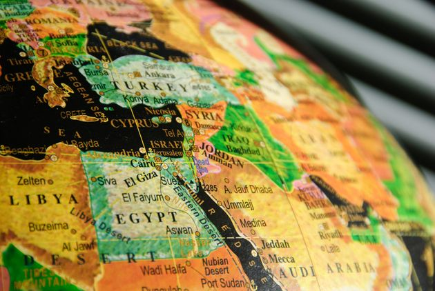 A portion of a colorful globe with a black water background showing the Middle East with particular focus...