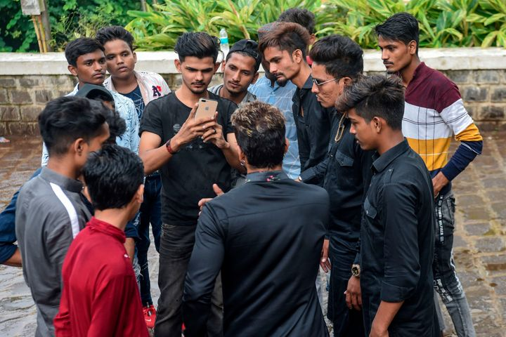 In this photo taken on November 10, 2019, youngsters gather around mentor Akhtar Shaikh (back to camera) before a video-recording session in Mumbai. Image used for representational purposes only in this article.
