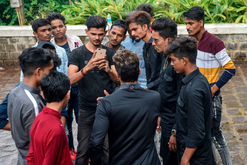 In this photo taken on November 10, 2019, youngsters gather around mentor Akhtar Shaikh (back to camera)...