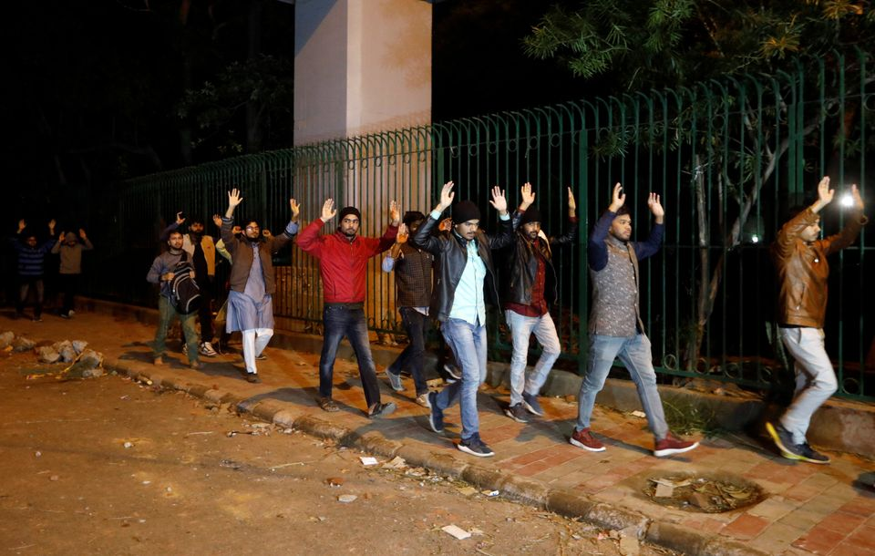 Students raising their hands leave the Jamia Milia University following a protest against a new citizenship...