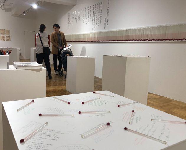 国境なき医師団の展覧会会場で、手間に温度計と主に色鉛筆で書かれた訪問者のメッセージ