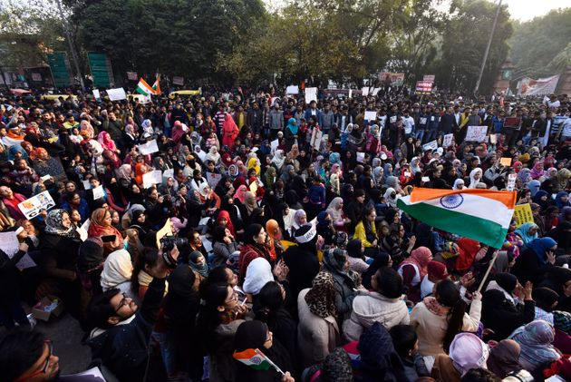 Hundreds of demonstrators shout slogans and hold placards as they attend a protest against a Citizenship...
