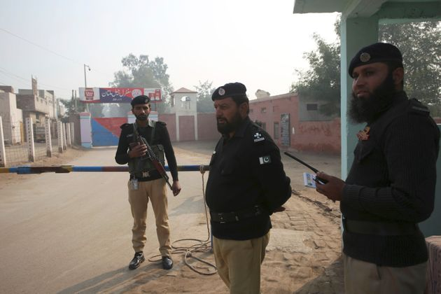 Pakistani police officers stand guard outside Multan jail after a court's decision for a professor facing...