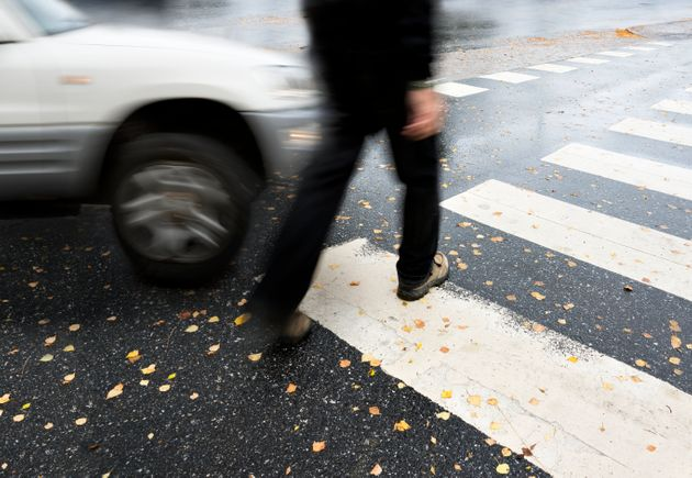 Man on pedestrian crossing in autumn, in danger of being hit by